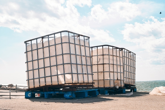 I believe these plastic bins are used at sea to pack the catch in ice. The cages are either used to lift the catch from the hold using winch systems, or they are used to store the fish after returning to port - I am not sure which.